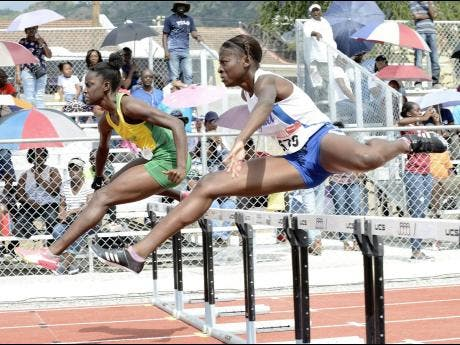 Rosalee Cooper (left) of St Jago High School and Hydel High's Taffara Rose battling for top spot in a heat of the Class One Girls 100me hurdles at the Purewater/JC/Danny Williams Invitational Development Meet at Jamaica College on Saturday, January 5, 2019.