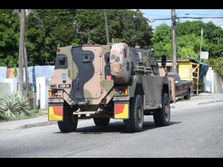 A Jamaica Defence Force vehicle is driven along Mountain View Avenue yesterday.