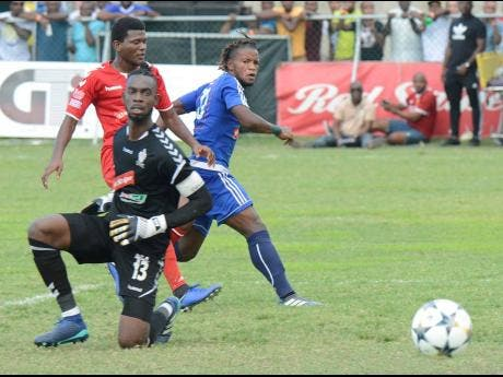 Mount Pleasant's Kemar Beckford (right), flicks the ball beyond advancing UWI goalkeeper Amal Knight (front) to score in their Red Stripe Premier League game at Drax Hall in St Ann on Sunday, March 31, 2019.