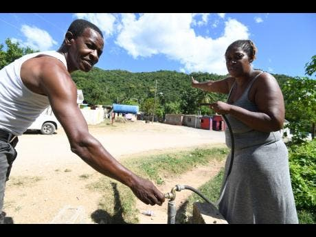 Wilburn Forbes and Susan Morgan show a pipe which gets water from the tank beside the community centre.