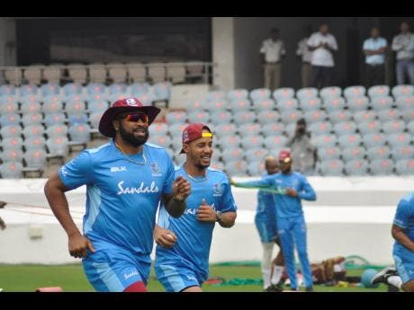 Windies One Day International and Twenty20 captain Kieron Pollard (left) and teammate Lendl Simmons warm up during a training session at the Rajiv Gandhi Stadium in Hyderabad, India on Tuesday, December 3, 2019.