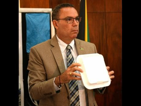 Daryl Vaz, minister with responsibility for the environment, displays a styrofoam box.