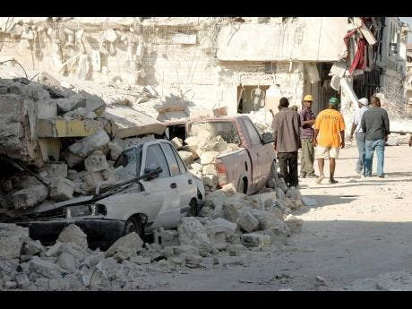 Survivors of the 2010 Haiti earthquake walk by motor vehicles crushed by a collapsed building shortly after the disaster which claimed hundreds of thousands of lives in that country 10 years ago.
