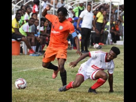 Tivoli Gardens captain Kemar Flemmings (left) evades a tackle from UWI's Nacquain Brown during their Red Stripe Premier League match at the Edward Seaga Complex yesterday.