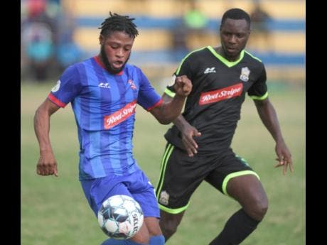 Molynes United's Shane Watson (right) tracks the run of Dunbeholden's Dean-Andre Thomas during their Red Stripe Premier League game at the Constant Spring field on Sunday, December 29, 2019.