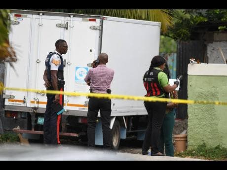 Police personnel on the scene of the  shooting death of 18-year-old Lavern Edwards on Escarpment Road, August Town, yesterday.