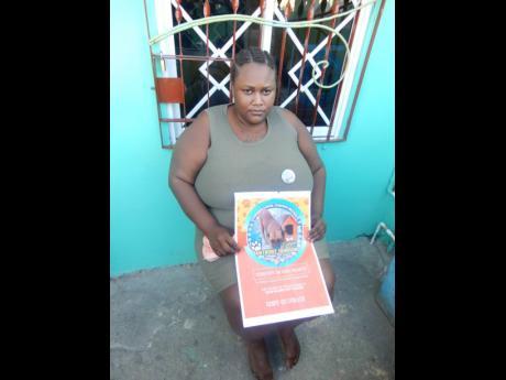 Camiesha Fletcher holds a photo of her beloved dog Backyard.