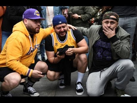 Los Angeles Lakers fans Alex Fultz, from left, Eddy Rivas and Rene Alfaro react to the death of former NBA player Kobe Bryant outside of the Staples Center prior to the 62nd annual Grammy Awards yesterday.