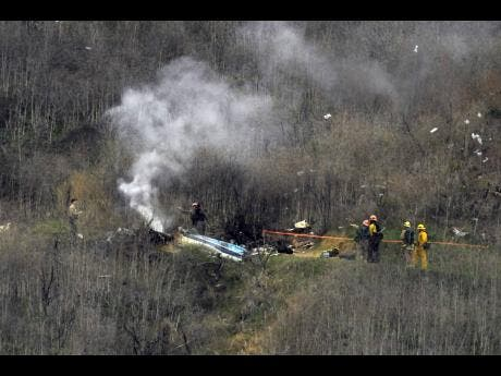 Firefighters work the scene of a helicopter crash Sunday, Jan. 26, 2020, in Calabasas, Calif. NBA basketball legend Kobe Bryant, his teenage daughter Gianna and three others were killed in the crash in Southern California yesterday. Left:  In this March 2, 2019 photo, Kobe Bryant and his daughter Gianna watch the first half of an NCAA college basketball game between Connecticut and Houston in Storrs, Connecticut.