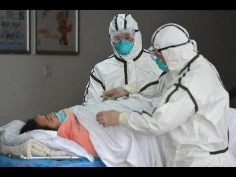 Medical workers in protective suits move a coronavirus patient into an isolation ward at the Second People's Hospital in Fuyang in central China's Anhui Province on Saturday.