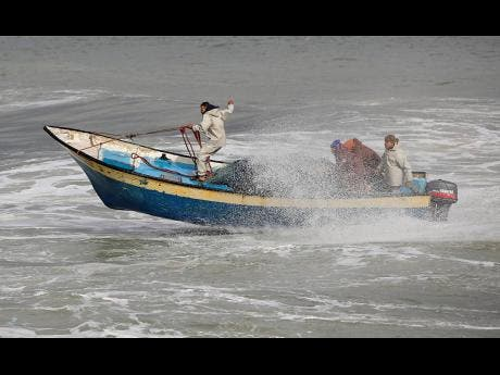 Palestinian fishermen ride their boat amid high waves on a windy and rainy day at the sea in Gaza City on Sunday.