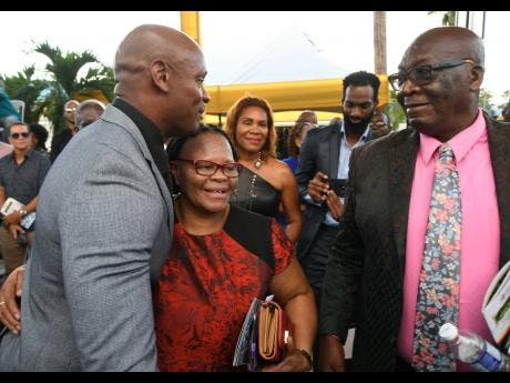 Asafa Powell shares a hug with his mother, Cislyn as his father William looks on before the unveiling of a statue of the former world record holder yesterday at Independence Park.