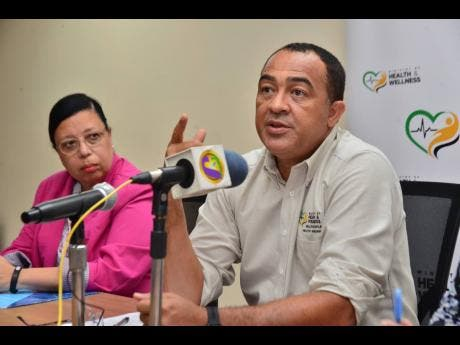 Health Minister Dr Christopher Tufton (right) gives an update on the coronavirus yesterday at the ministry's New Kingston office. Looking on is Bernadette Theodore - Gandi, PAHO/WHO representative to Jamaica, Bermuda and the Cayman Islands.