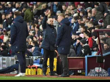 Tottenham's manager Jose Mourinho (centre) gestures in front of Aston Villa's head coach Dean Smith, right, during the English Premier League match between Aston Villa and Tottenham Hotspur at Villa Park in Birmingham, England, yesterday.