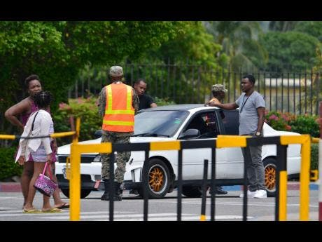Military police at the Jamaica Defence Force Up Park Camp base search vehicles leaving the facility after two weapons were discovered missing.