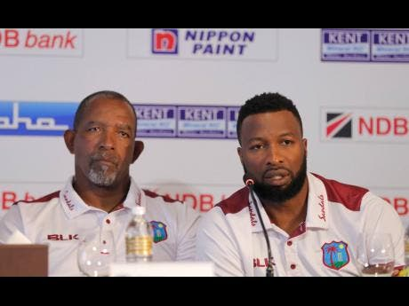 West Indies' cricket captain Kieron Pollard (right) speaks to media as coach Phil Simmons looks on during the inauguration of NDB series trophy in Colombo, Sri Lanka, on Wednesday.