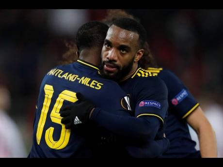 Arsenal's Alexandre Lacazette (right), scorer of  his team's winning goal, celebrates with teammate Ainsley Maitland-Niles after the end of a Europa League round-of-32, first leg, match against  Olympiakos in Athens, Greece.  Arsenal won 1-0.