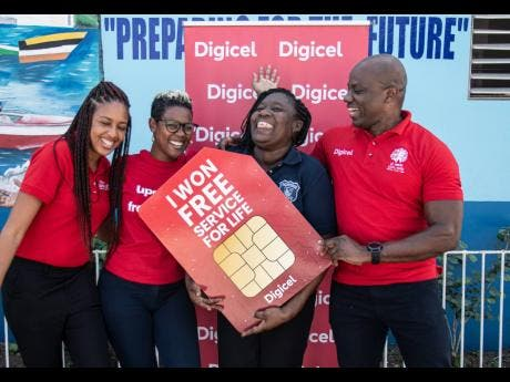 """It was a super happy moment for Digicel customer, Andrene Holness (second right), when she officially received her """"Free Mobile Service for Life"""" prize from Digicel Public Relations and Communications Manager, Elon Parkinson (right), Brand Marketing Manager, Michaela Francis (second left), and Digital Media Executive, Kadeen Brown."""
