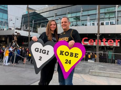 Alyssa Shapiro (left) of Huntington Beach, and her father Rick Shapiro stand outside Staples Center in Los Angeles, California, before a public memorial for Lakers legend Kobe Bryant and his daughter, Gianna, yesterday. The family's love of the game – and Bryant's work in women's sports – prompted Alyssa to become a middle school girls' basketball coach.