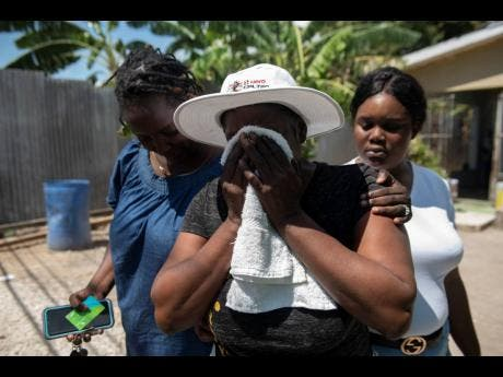 Marjorie Powell (centre) is overcome with grief as she mourns the loss of her son Irvino English, a former national football player. Powell is consoled by Tina Palmer (left) and Alicia Breakenridge.