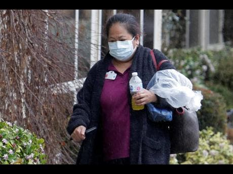 A worker wears a mask at the Life Care Center in Kirkland, Washington, near Seattle, yesterday. Several of the people who have died in the state from the COVID-19 coronavirus were tied to the long-term care facility, where dozens of residents were sick.