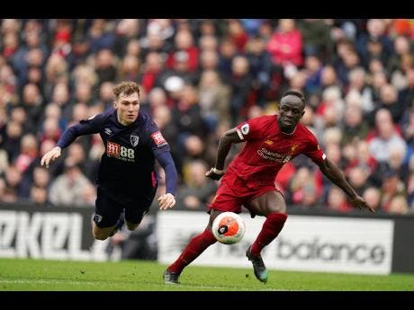 Liverpool's Sadio Mane, right, dribbles past Bournemouth's Jack Stacey during the English Premier League match between Liverpool and Bournemouth at Anfield stadium in Liverpool, England, Saturday, March 7, 2020.
