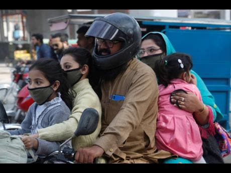 A Pakistani family wears face masks to help prevent exposure to the new coronavirus as they travel on a motorbike in Lahore, Pakistan, yesterday.