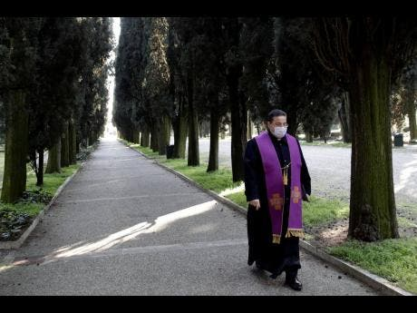A priest wearing a mask walks in the Vantiniano cemetery in Brescia, Italy, Monday, March 16. For most people, the new coronavirus causes only mild or moderate symptoms. For some, it can cause more severe illness, especially in older adults and people with existing health problems. Italy recorded 368 deaths in 24 hours due to coronavirus, bringing the total number dead to 1,809. In Spain, the death toll doubled in a day.
