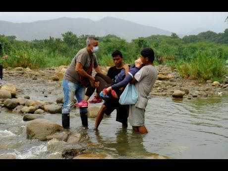A Venezuelan woman is helped by men as they cross illegally into Colombia from Venezuela, near the Simón Bolívar International Bridge in La Parada near Cúcuta, Colombia, on Saturday. Colombian President Ivan Duque has ordered the nation's border with Venezuela closed as a coronavirus containment measure.