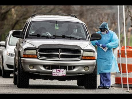 A man and woman get tested for COVID-19 at a drive-through testing site at Cone Health Ambulatory and Physician Services in North Carolina, yesterday.