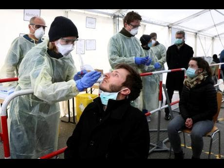 Medical employees demonstrate testing, at a coronavirus test center for public service employees, during a media presentation in Munich, Germany on Monday.