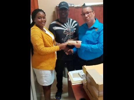 Clint Rennie (centre) donates cheque for $163,000 to the Falmouth Infirmary. Accepting the cheque is matron Tracey-Ann McGlashan and Andrew Harrison of The Trelawny Municipal Corporation.