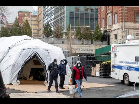 Medical and construction workers are seen at the site of a makeshift morgue that was built outside a hospital in New York on Wednesday.