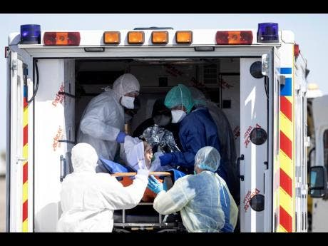 Medical staffs evacuate a patient infected with the Covid-19 virus from an ambulance before transporting him into a French military helicopter heading to Switzerland.