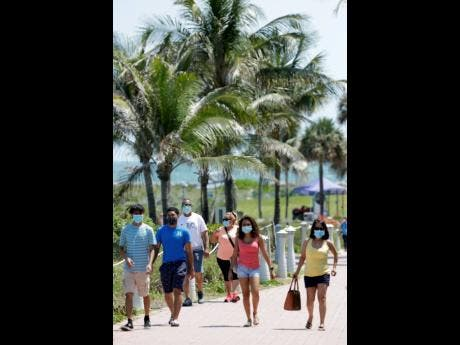AP Photo Beachgoers wear face masks as they walk along a path yesterday in Miami Beach, Florida.