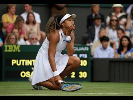 Japan's Naomi Osaka reacts as she plays Kazakstan's Yulia Putintseva in a women's singles match during day one of the Wimbledon Tennis Championships in London last July.