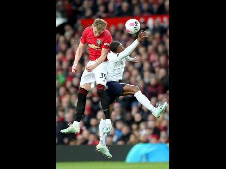 Manchester United's Scott McTominay (left) jumps for a header with Liverpool's Sadio Mane during their English Premier League match at the Old Trafford stadium in Manchester, England, in October  2019.