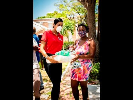 D'Angel (left) donates a care package to a resident of Spanish Town.