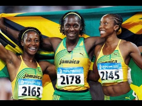 Jamaica's gold medallist Shelly-Ann Fraser (left) and silver medal winners Kerron Stewart (centre) and Sherone Simpson celebrate after the women's 100-metre final at the 2008 Beijing Olympic Games.