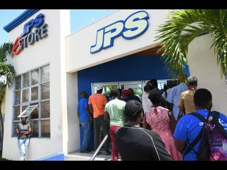 Customers of the Jamaica Public Service Company gather outside its Ruthven Road, Kingston offices on, March 23.