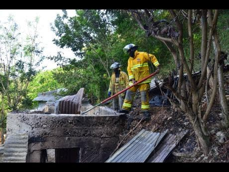 Firefighters conduct cooling down operation at this house in Burnside Valley, Red Hills, St Andrew, yesterday.