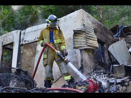 Fire ravaged this two-bedroom house in Burnside Valley, Red Hills, St Andrew, yesterday.