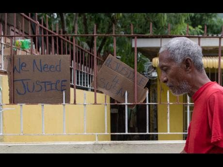 A man walks by a sign in August Town, St Andrew, which underscores te residents cry for justice.