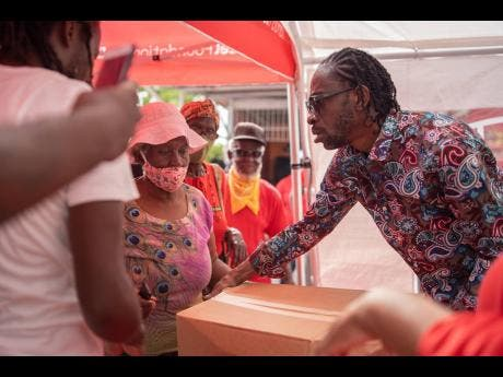 Bounty Killer donates grocery items to a resident of the Majesty Gardens community.