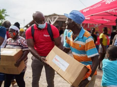 Public Relations and Communications Manager for Digicel, Elon Parkinson, assists Majesty Gardens senior citizen Aston Lawrence with getting a ride home after he received his care package from the Digicel Foundation and Bounty Foundation.