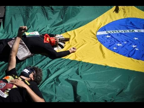 Protesters lay down on the Brazilian flag during a protest against racism, the policies of President Jair Bolsonaro's government, and to defend democracy amid the new coronavirus pandemic at the Ministries Esplanade, in Brasilia, on Sunday.