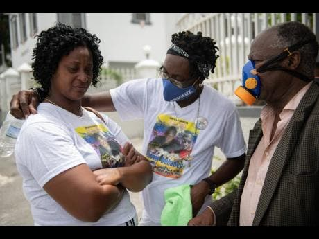 Yanike Crosdale (left), mother of the late Jevaughn Duhaney, is consoled by Leon Duncan (centre) as they wait for Duhaney's autopsy to be done at the House of Tranquillity Funeral Home in Kingston yesterday. Looking on is Dr Jephthah Ford.