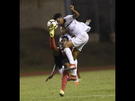 File In this file photo from November 2017, Arnett Gardens' Tamar Edwards (left) and Alex Marshall of Cavalier put their bodies on the line for possession during a Red Stripe Premier League game at the Stadium East Field in Kingston.