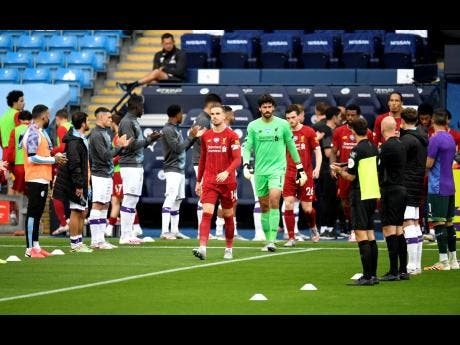 Liverpool players walk through a guard of honour from the Manchester City team ahead of their English Premier League match at Etihad Stadium in Manchester, England, Thursday, July 2, 2020.