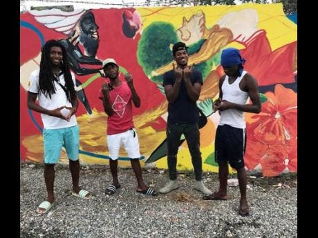 An elated Conroy Green (second right) poses for a photo with other LifeYard members (from left) Romaine 'Sabukie' Allen, Shasane Parker, and Odane Stone, in front of their newly painted mural in Rockfort, east Kingston.